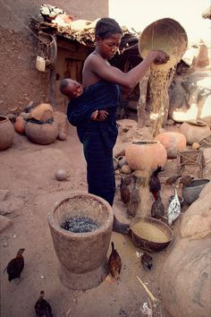 Africa | Dogon woman preparing millet with her child on her back. Mali. | © Bryan & Cherry Alexander Photography / ArcticPhoto