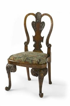 A fine George I Irish carved walnut side chair, the waisted cartouche shaped back with scallop shell cresting above an acanthus and paper scroll carved vase-shaped splat and balloon shaped seat rail with drop-in needlepoint pad with (restored) early floral woolwork cover, on bold eagle mask carved cabriole legs with trailing acanthus, ending in upswept scroll feet , the plain tapering rear legs on pad feet