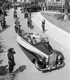Prince Ranier III and Princess Grace (nee Kelly) are driven through Monaco in an open Rolls Royce with official escort April 19th, 1956, after they were wed in the Cathedral of St. Nicholas.