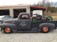 Flat black Chev chevy chevrolet advanced design pickup truck with orange wheels and custom doorr graphics ams a custom hardtail motorcycle chopper in the bed.