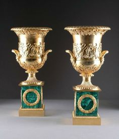 """A Pair of Rare Estate Museum Quality European Gilt Bronze and Malachite Two Handled Urns. The circular tapering body centering a continuous band of dancing maidens beneath a flaring top of grape cluster and vine beneath an egg and dart rim above an acanthus and flower cast base on a circular petal form socle and a rectangular pedestal enclosing berried laurel wreaths. 23 1/8""""H x 11 3/8""""Diam."""