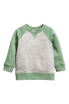 Gray melange/light green. CONSCIOUS. Soft, organic cotton sweatshirt with snap fasteners on one shoulder (sizes 9 - 24 months without snap fasteners) and