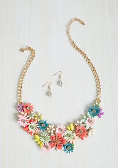 By parading this statement necklace and teardrop-shaped earrings, you're planting a seed in others to sass up their style with florals! Showcasing a mix of pastel petals and bright blossoms - all bedazzled with rhinestone centers and supported by golden curb chains - this accessory grows smiles.