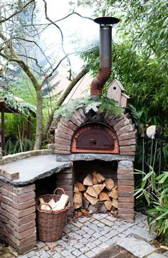 Rustic pizza oven surrounded by lush plants. Add colorful tiles and it would be perfection.