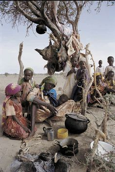 Darfuri women and children wait outside a refugee camp in Bahai, Chad