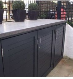 Garden storage unit made from wood with an industrial look zinc top. A stylish way to hide a bin or store a bike.
