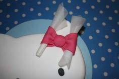 bow with two oval pieces of pink icing. Each piece is folded in half and bunched up in the middle. I then positioned a ball of pink sugar paste on top where the two 'ovals' meet, hiding the join. Stick it to the cake with a little royal icing. Roll up some baking paper and slip a piece into each bow to hold it a little open allowing it to dry in that position. You can remove it after a few hours. I leave it over night.