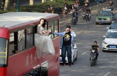 Magician Lei Xin (R) is seen suspended outside a double-deck bus, next to a woman in a wedding gown, as they participate in a performance on a street in Zhengzhou, Henan province, China, October 15, 2015. According to local media, the performance, organized by Lei and his friends, is aiming to promote a healthier view of love and marriage among young people. REUTERS/Stringer