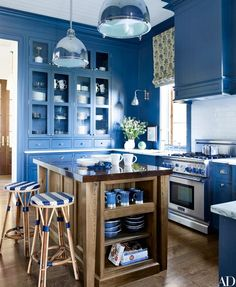 At a Maine compound renovated by designer Suzanne Kasler and architect Les Cole, the poolhouse kitchen features Urban Archaeology pendant lights, a Thermador range, sink fittings by Michael S. Smith for Kallista, and counter stools from Walters   archdigest.com
