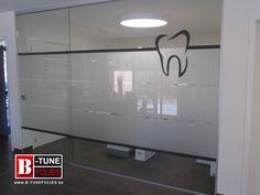 Glazen wandpaneel bij een tandartspraktijk, voorzien van matte raamfolie en een belettering gesneden folie, tand.