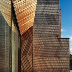Herringbone Houses by Allison Brooks Architects. Each open-plan house is composed of two continuous planes of herringbone timber and graphite render surfaces that form walls, floors, external decking and fences. These planes interlock and fold inward at the centre of the house to create a double height entrance hall open to the sky.