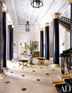 In the entrance hall, original features—including the columns, overdoor panels, and balustrade—make a noble setting for vintage Gilbert Poillerat lanterns, a 1939 Fernand Léger painting, a '30s Jansen center table from Liz O'Brien, and Italian benches cushioned in a Clarence House horsehair.