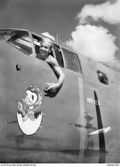 "McDonald, Nt. 1943-05-04. Sergeant G. Wynnands in the cockpit of a North American B25 Mitchell bomber aircraft, number N5-128 of No. 18 (Netherlands East Indies) Squadron, pointing to the aircraft's emblem ""Donald Duck"", an example of nose art"