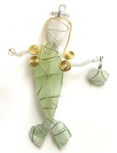 Sea glass is sometimes known as mermaids tears, so this whimsical mermaid was created with this in mind. Her body is seafoam green, and she holds an