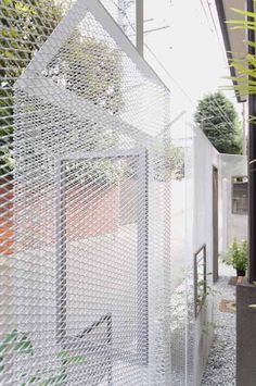Japanese architects Shingo Masuda and Katsuhisa Otsubo have installed mesh screens at the boundary of a property in Tokyo. Called Ghost-like Architecture, the screens are made of expanded metal and act as louvres. The property boundary therefore appears to be surrounded by an opaque wall when viewed from one angle, but a translucent mesh from