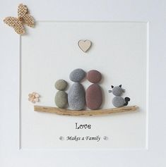 This is a beautiful Large Square Pebble Art framed Picture of a Little Family with a Cat - Love makes a Family handmade by myself using Pebbles, Driftwood, Wooden Heart, Embellishements Size of Picture incl Frame : approx. 25cm x 25cm This Picture is finished and only available as shown in
