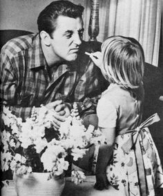 Robert Mitchum and daughter Trina photographed in Photoplay, 1956.  Original caption: A self-styled cynic — but Bob's reduced to abject slavery by a pat of his baby daughter's chubby hand.