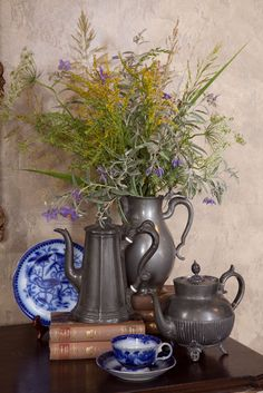 Beautiful balanced layering of objects here. Colorful sprigs of wheat and other wild flowers make for a simple and whimsical arrangement in these pewter culinary antiques.