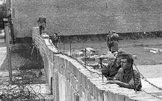 Policiais da Alemanha Oriental removem barbante de um muro enquanto, ao fundo, colegas aumentam a parede para 15 metros de altura na Bernauer Strasse, em Berlim, em foto de setembro de 1961