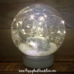 This clear plastic waterless snow globe displays a sparkling winter wonderland snow scene. A perfect gift for the holidays or new addition to your holiday decor.  Available with polar bear, miniature wooden train, or frosted trees. Other objects may be available for customization.  Pre-lit with warm fairy string lights. LED filaments last up to 80,000 hrs. 2 x CR2032 batteries (replaceable) included*. Batteries last up to 30 hours. Battery pack and On/Off switch located in screw off base...