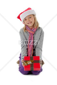portrait of a smiling girl with her christmas gift. - Portrait of a smiling girl with her christmas gift kneeling over white background, Model: Alyssa Power