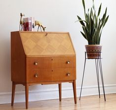 This mid-century modern teak secretary desk features a a drop-down cabinet with a crosshatch pattern and vintage key to unlock the top drawer.