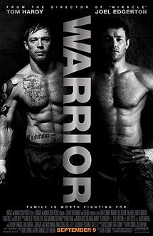 """Two shirtless, muscled men stand against a black background. The word """"Warrior"""" is written sideways between them."""