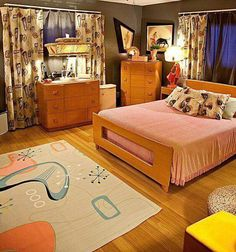 This looks like the bedroom of a kid from the '60s or '70s that has a band, cool sneakers and is in love with the prettiest cheerleader in school. The hardwood floor is a perfect base for the funky retro patterned carpet and the more subdued but still delightfully retro bedspread. The curtain pattern matching the throw pillows is a great touch.