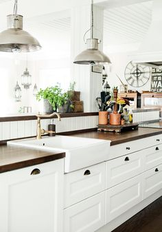 Farmhouse apron sink, white cabinets, dark butcher block counters and a gold sink faucet ♥️