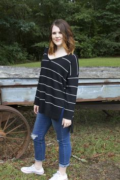 Loving our Between the Lines Sweater for fall! This v-neck sweater has an over-sized bodice and side slits for a roomy fit. Model is wearing a small and our Kendall skinny jeans! Shop at SHOPMADMARYS.COM