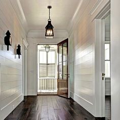 Shiplap lining the halls to a stunning porch lantern! #Bevolo French Quarter on a ladder rack.@robynhoganhome