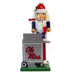 Mississippi Tailgating Nutcracker Christmas Decoration 12 nutcracker (decorative only) on a 5 x 5 base. Dressed in white apron with Ole Miss logo. Wearing a Santa hat and cooking hotdogs on a grill with Ole Miss logo on front.