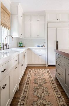 Sunny white kitchen featuring white cabinets, fronted refrigerator, and quartz countertops, a butcher block countertop on the island, medium tone hardwood floors and a light colored woven rug - Kitchen Ideas & Decor