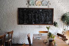 Lousa com divisão de convidados nas mesas do restaurante. Mini wedding romântico e rústico com toques cobre e decoração verde e branca.
