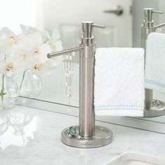 HANDI is a new family of vanity-top organizers. The Hand Washing Valet is an innovative fusion of a soap dispenser and vanity towel stand into one compact organizer. This all-in-one station dispenses hand soap and keeps your towels at a fingertip's distance away. It even includes a tray to rest your rings and other jewelry. The HANDI Hand Washing Valet is an elegant space-saving solution that will simplify your daily routine and makes life a little easier.