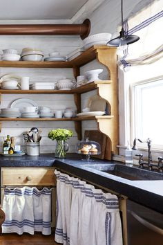 5. Reclaimed shelves: Made of Belgian pine and supported by brackets carved from single pieces of wood, the shelves once hung as a 6-foot-wide single unit in Dianne's barn. Her son-in-law, builder Darryl McCreary, carefully cut them to wrap the corner. (For similar shelves, try wayfair.com.) 6. Concrete countertops: At 4 inches thick, this custom-colored concrete was inspired by antique soapstone. 7. Skirted storage: The striped panels are made from an old linen tablecloth. (For similar…