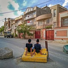 Two teenage Boys are resting on a Stone near their Home in Sinê, the Capital of the Province Kurdistan.