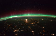 A view of Earth, the stars, and red and green auroras above cities in western North America, as seen from the International Space Station, on February 19, 2012. (NASA)