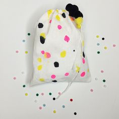 acrylic paint on a muslin bag plus pom poms. wrapping by ashley g