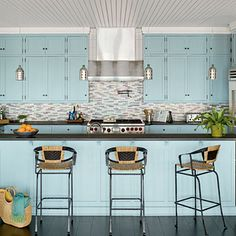 This kitchen's stainless steel appliances and dark surfaces are expertly balanced by the pale blue cabinetry and sea-inspired backsplash. | Coastalliving.com