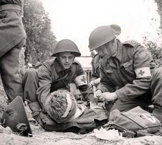 """According to the caption attached to this image, """"Canadian medics help a wounded soldier - Juno Beach, D-Day June Visuals such as this promote the idea that war doesn't only involve the 'killing' but the 'saving' as well. Canadian Soldiers, Canadian Army, British Army, British Tanks, World History, World War Ii, D Day Normandy, Combat Medic, Army Medic"""