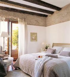 Dormitorio con parte de la pared de ladrillos a la vista y vigas de madera
