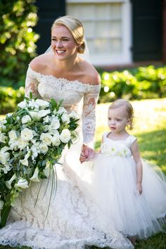 Bride in off shoulder wedding dress with young flower girl