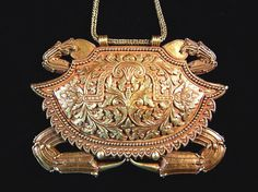 """The FRONT of a pendant (on a chain, thus forming a necklace with that) posted by Linda Pastorino on her page of """"ethnic jewels"""". She describes the assembly as a """"22K royal crabnecklace measuring 6 inches across"""". It is apparently from Sumatra, and in her caption for the image of the BACK she describes it as 17th c. Richter-Carpenter has a somewhat similar example on p. 255, described as Makassar and thus from Sulawesi; it is dated 19th c. The Bugis also made these pieces."""