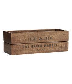 Donkerbruin. Een rechthoekig kistje van hout met een antieklook. Het kistje heeft een tekstprint op de voorkant en pads aan de onderkant. Vanwege de