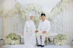 Bride and groom posing against their beautifully-decorated dais in all white at the Ba'alwie Mosque // Razif and Sarah decided to celebrate their Singapore wedding solemnisation, or nikah, at Ba'alwie Mosque in a meaningful and intimate ceremony captured by Zakaria Zainal of We Made These. The couple looked resplendent in all white against the immaculate dais decorated by Fleursdeco and the bridesmaids stood out with pops of colour from batik skirts