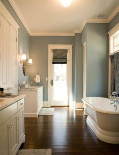 Mitch Wise Design: Sophisticated master bathroom with freestanding tub, blue paisley fabric cafe curtains--dark hardwood in bathroom?