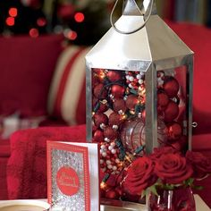 Christmas lantern, filled with various holiday decor and a strand of lights.