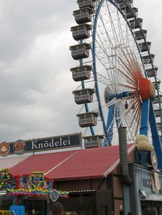 """Zwischen Riesenrad und Wahnsinns-Rotations-Schleuder-Gerät die """"Knödelei"""" ...  Wer holt sich einen Knödel? Aus dem Riesenrad raus oder mit zum Münchner Überblick ... zum Schwindel-Überschlag nebenan wohl weniger empfehlenswert, sonst fliegen die Knödel gleich wieder zur Knödelei zurück ... und ob die Überflieger nach dem Ausstieg Appetit auf Knödel haben ...?"""