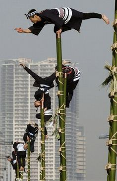 Japanese fire fighters wearing traditional costumes displayed display their balancing skills atop bamboo poles during an annual New Year demonstration in Tokyo